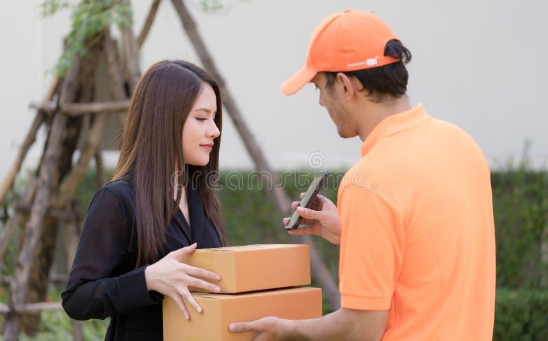 Fattorino che chiede la firma per la consegna del pacchetto immagini stock