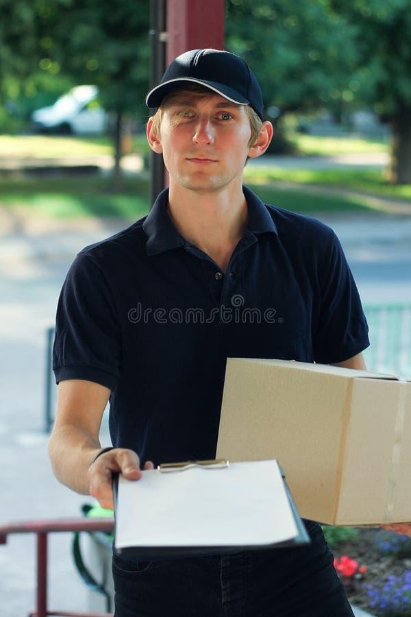 Fattorino che consegna il contenitore di pacchetto al proprietario di abitazione immagini stock