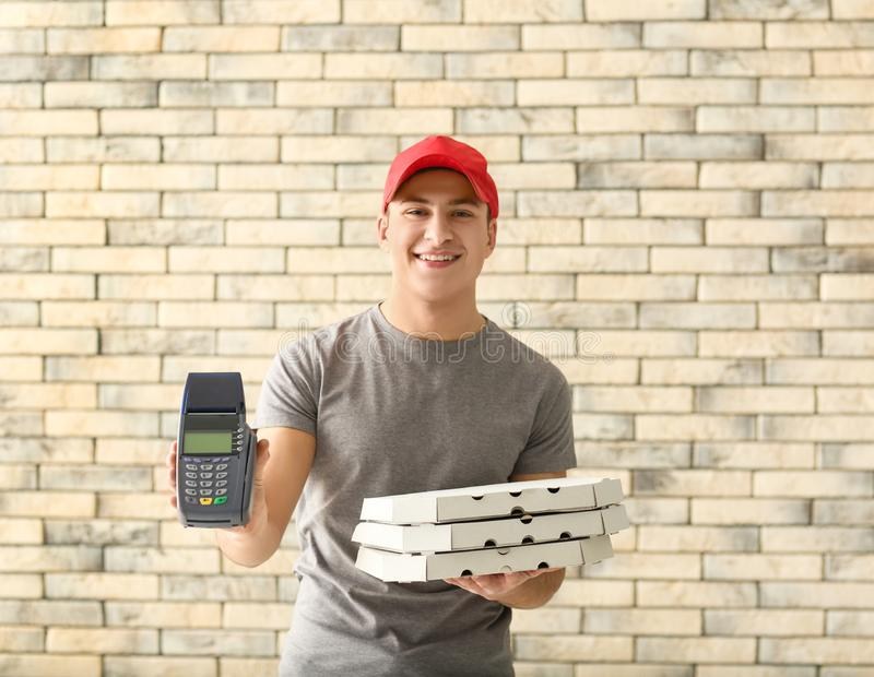 Fattorino con i contenitori di pizza del cartone ed il terminale di pagamento sul fondo del muro di mattoni fotografie stock libere da diritti