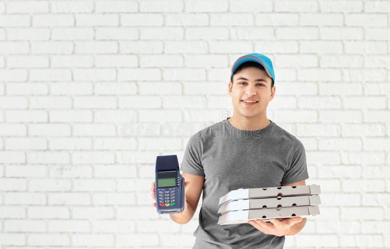 Fattorino con i contenitori di pizza del cartone ed il terminale di pagamento sul fondo del muro di mattoni fotografie stock