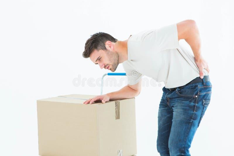 Fattorino con la scatola di cartone che soffre dal mal di schiena fotografia stock libera da diritti
