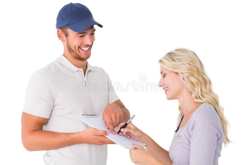 Fattorino felice che ottiene firma dal cliente fotografia stock libera da diritti