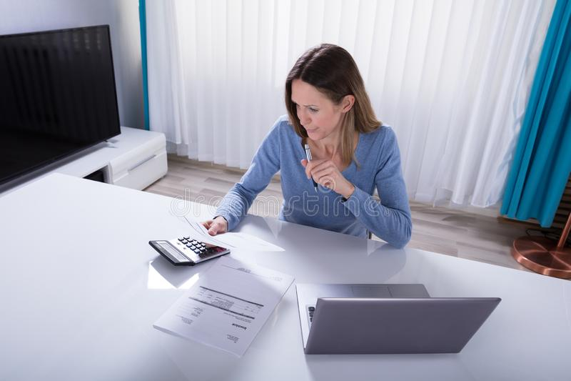 Fattura calcolatrice della donna con il calcolatore a casa fotografie stock libere da diritti
