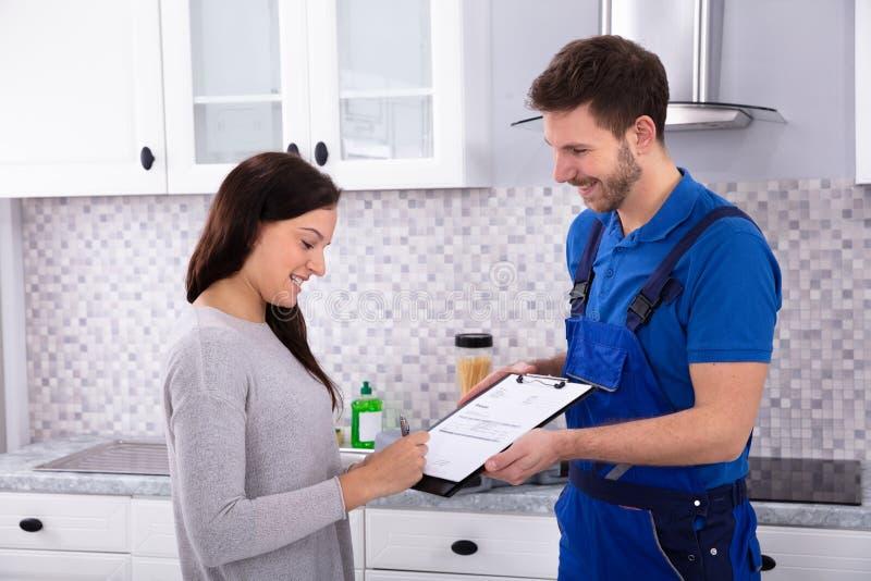Fattura di firma della donna in cucina immagini stock