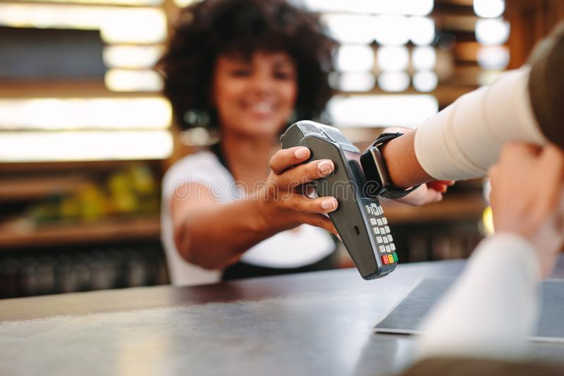 Fattura di pagamento del cliente facendo uso di uno smartwatch immagini stock
