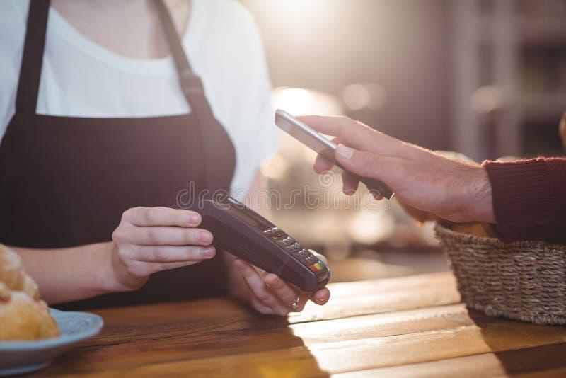 Fattura di pagamento del cliente tramite lo smartphone facendo uso di tecnologia di NFC fotografia stock libera da diritti