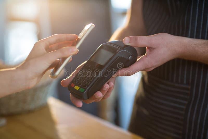 Fattura di pagamento della donna tramite lo smartphone facendo uso di tecnologia del nfc fotografia stock libera da diritti