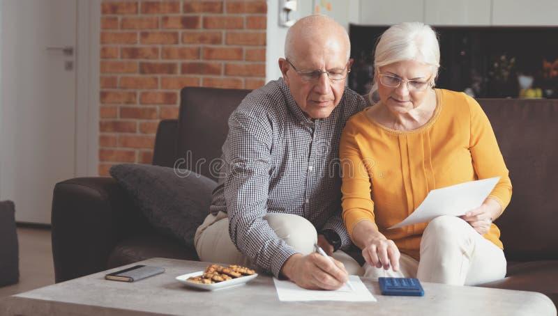 Fatture di pagamento senior delle coppie insieme fotografie stock