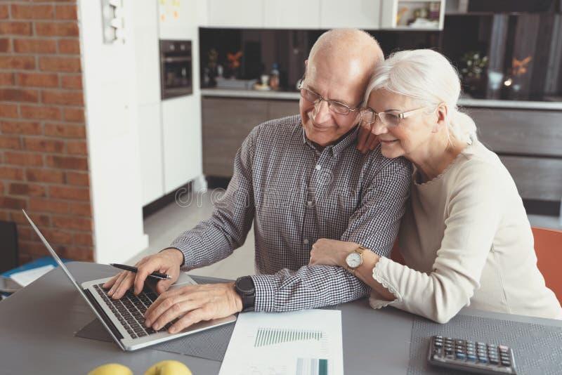 Fatture di pagamento senior delle coppie insieme sul computer portatile immagini stock libere da diritti