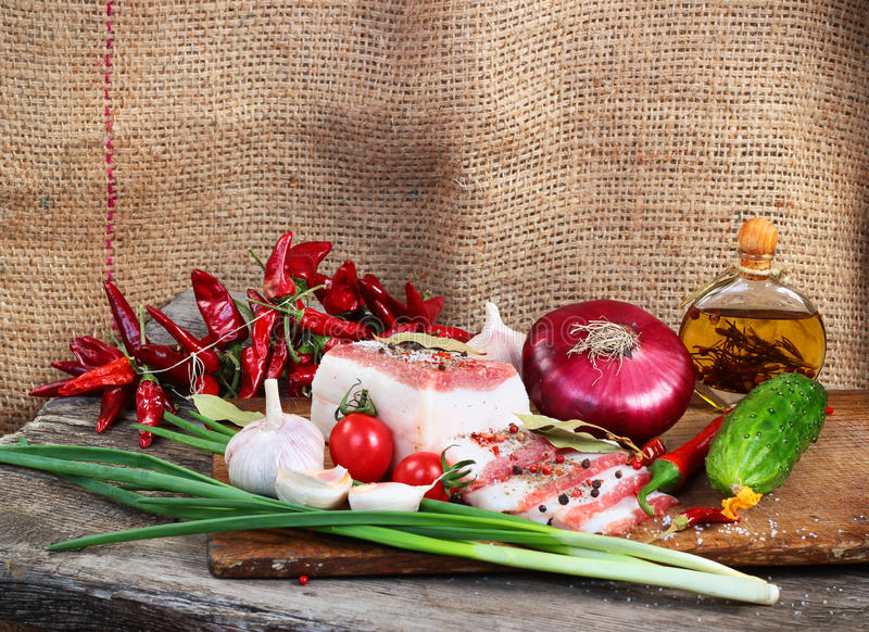 Fatty bacon with green and red vegetables on chopping board against burlap sack background.  stock photo
