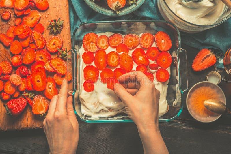 Fatura do bolo do tiramisu da morango As mãos fêmeas da mulher colocaram morangos no bolo no fundo de madeira rústico escuro, vis imagens de stock