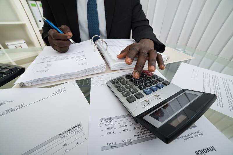 Faturas calculadoras do homem de negócios fotos de stock royalty free