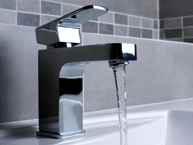 Faucet. Modern bathroom chrome faucet with running water royalty free stock photos