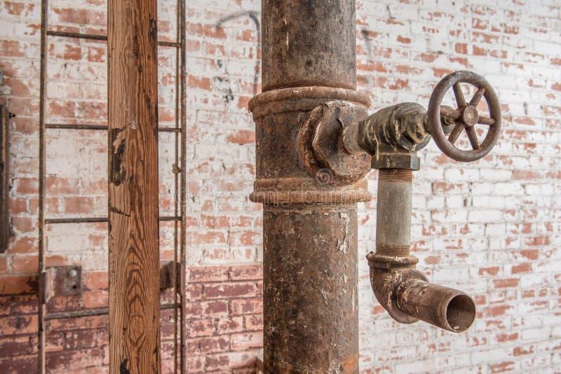 Faucet i drymba z drabiną na czerwonym ściana z cegieł zdjęcie royalty free