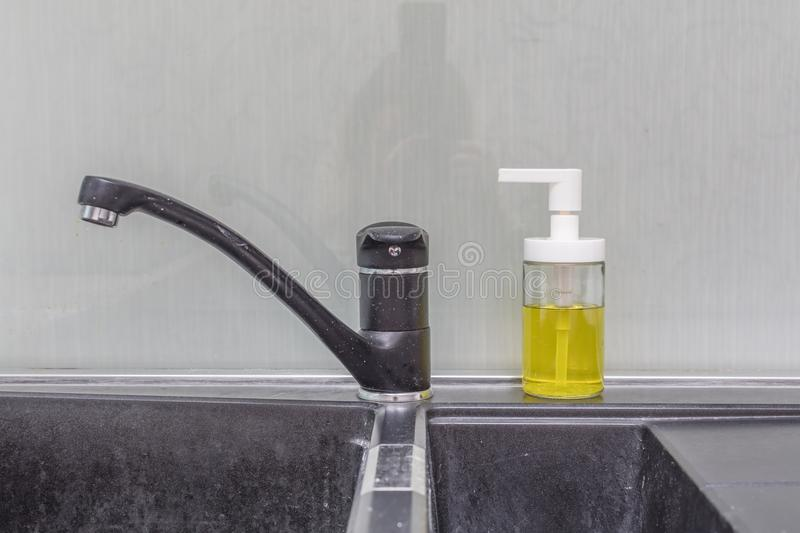 Faucet in kitchen. Close up of modern faucet and ceramic sink in kitchen stock photography