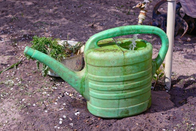 Faucet nalewa wodę w zieloną brudną plastikową podlewanie puszkę na ziemi zdjęcie stock