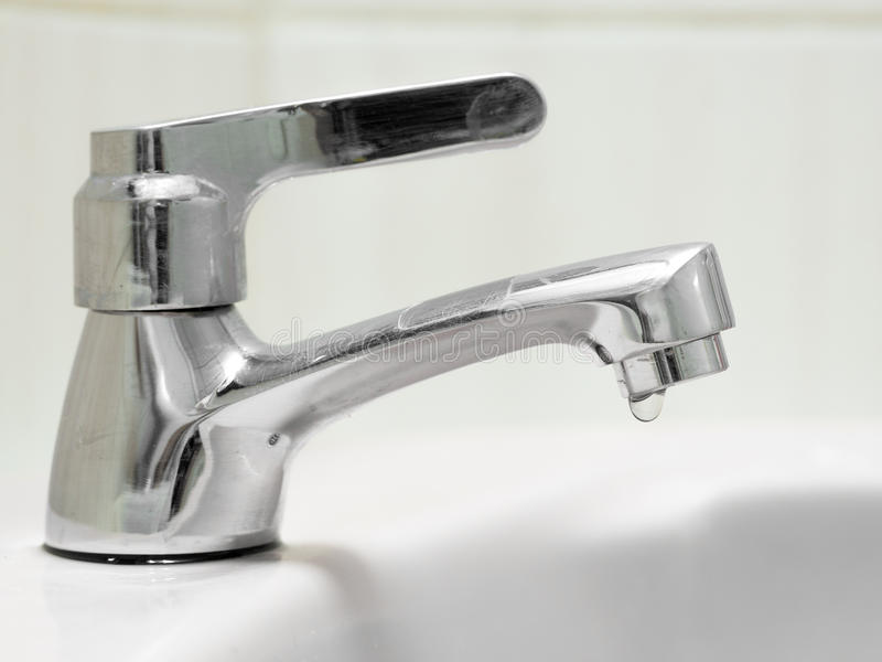 The faucet is not properly closed, the water is draining from the tap. stock images