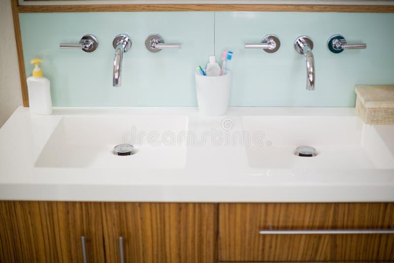 Faucets раковины с рукой моют, зубная щетка и зубная паста в ванной комнате стоковое изображение rf