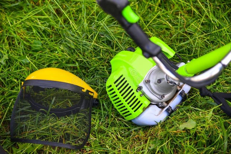 Faucheuse d'essence et masque protecteur sur l'herbe images stock