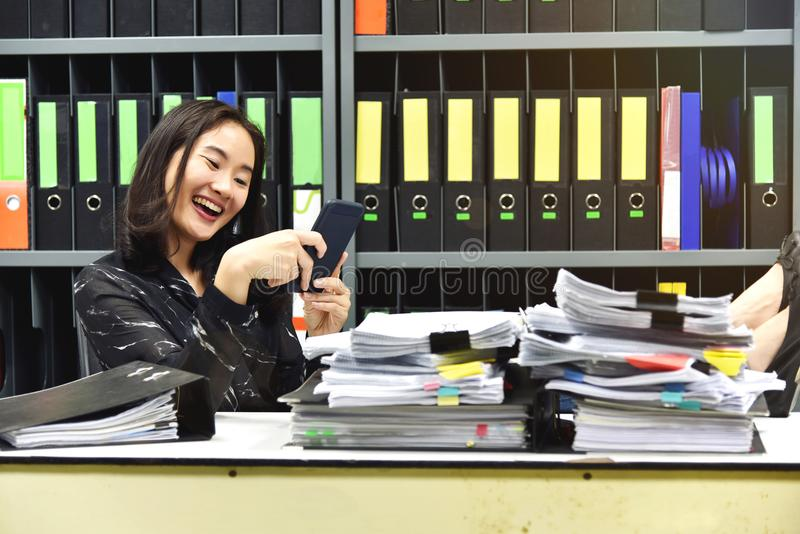 Faule asiatische Bürofrau, die intelligentes Mobiltelefon in der Arbeitszeit verwendet lizenzfreie stockfotos