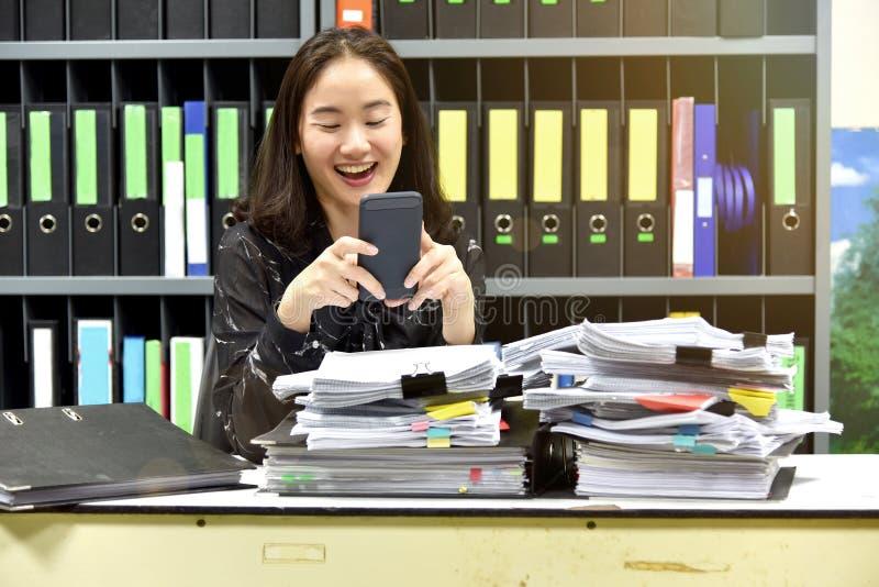 Faule asiatische Bürofrau, die intelligentes Mobiltelefon in der Arbeitszeit verwendet stockfotos