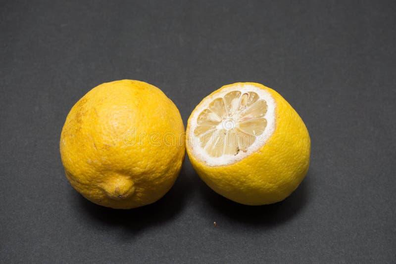 Faule Zitrone auf schwarzem Hintergrund lizenzfreie stockbilder