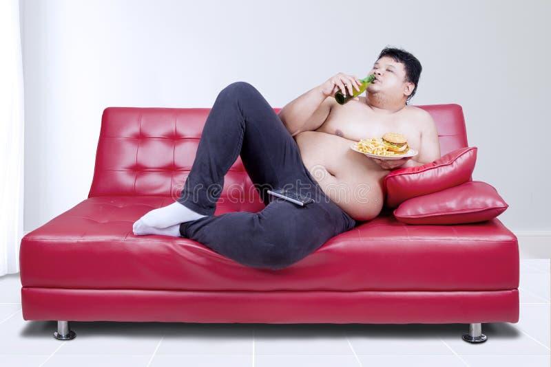 Fauler dicker Mann, der auf Couch stützt stockfoto