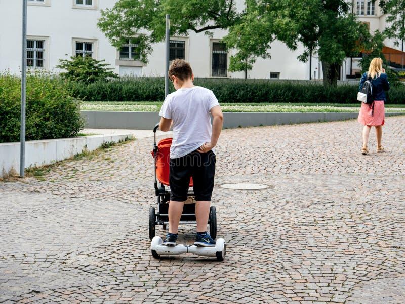 Fauler junger Mann, der Wagenspaziergänger drückt lizenzfreie stockfotos