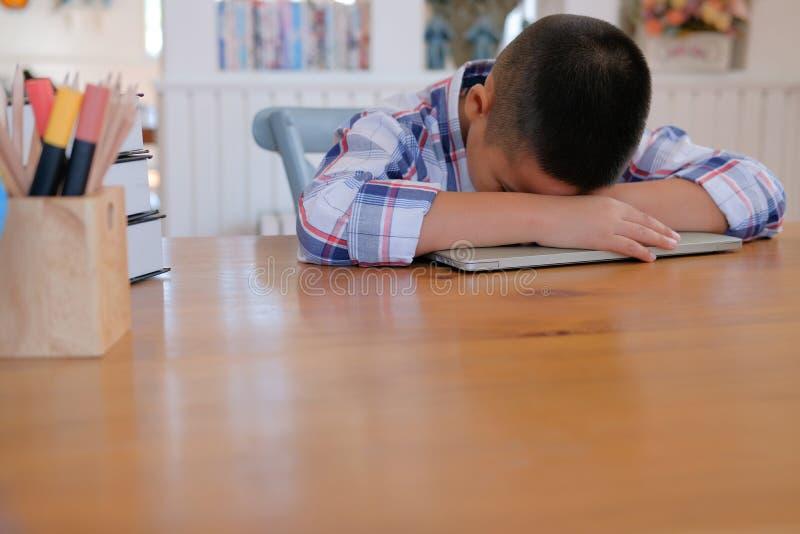 faules betontes stillstehendes Schlafen des jungen kleinen asiatischen Kinderjungen auf De lizenzfreies stockbild