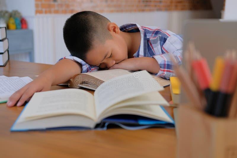 faules betontes stillstehendes Schlafen des jungen kleinen asiatischen Kinderjungen auf De lizenzfreie stockfotos