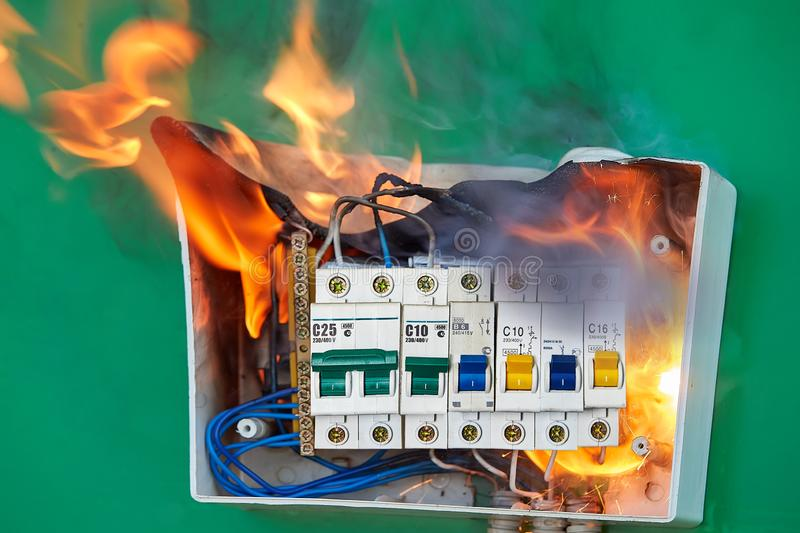 Home electrical fire started in electric fuse box. Faulty wiring became the cause of distribution board  fire. Bad electrical wiring systems caused fire inside stock photography