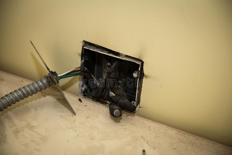 Melted wires after internal wall fire. Faulty wiring in the house caused a fire behind the wall. caused the wires to fuse together stock photo