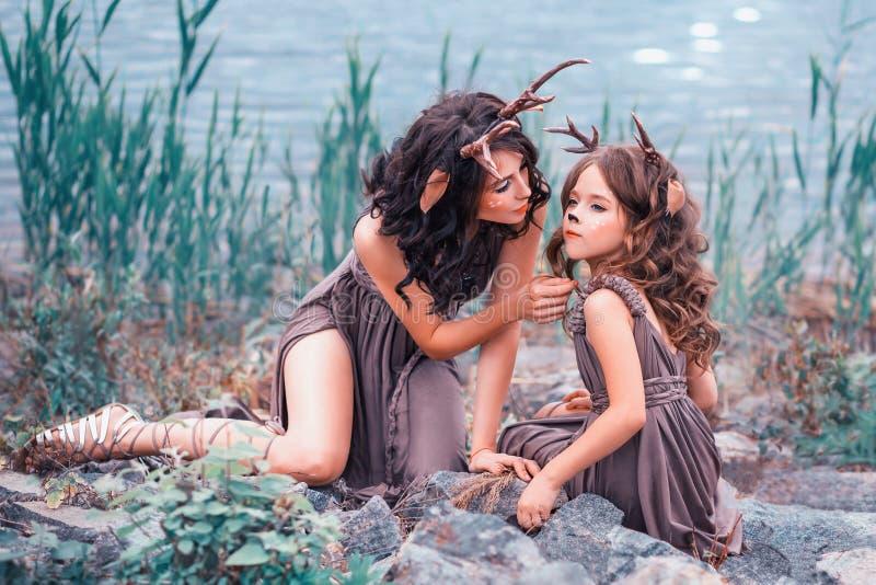 Faunas matka i dziecko siedzą na skałach na banku rzeka rodziców spojrzenia po jej dziecka dziewczyny zdjęcie royalty free