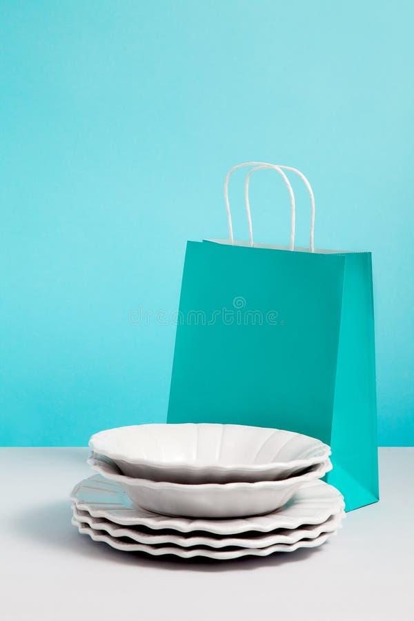 Fausse image haute avec la vaisselle en c?ramique pr?s du support de sac de papier sur le fond bleu Image de concept de cadeau av photos libres de droits