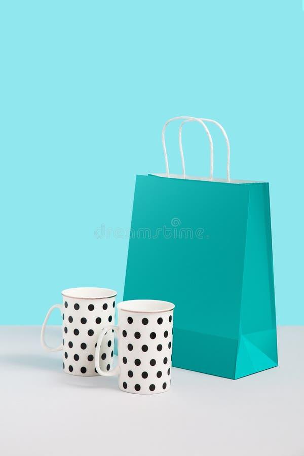 Fausse image haute avec tendre des tasses de th? pr?s de support de sac de papier sur le fond bleu Image de concept de cadeau ave images libres de droits