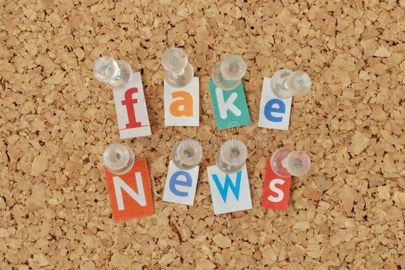 Fausses actualités de mots écrites avec les lettres coupées de magazine sur le bulleti photos libres de droits