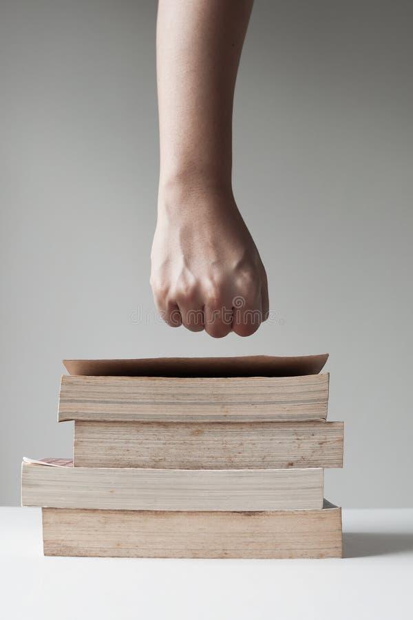 Faust über Stapel des Buches stockfoto