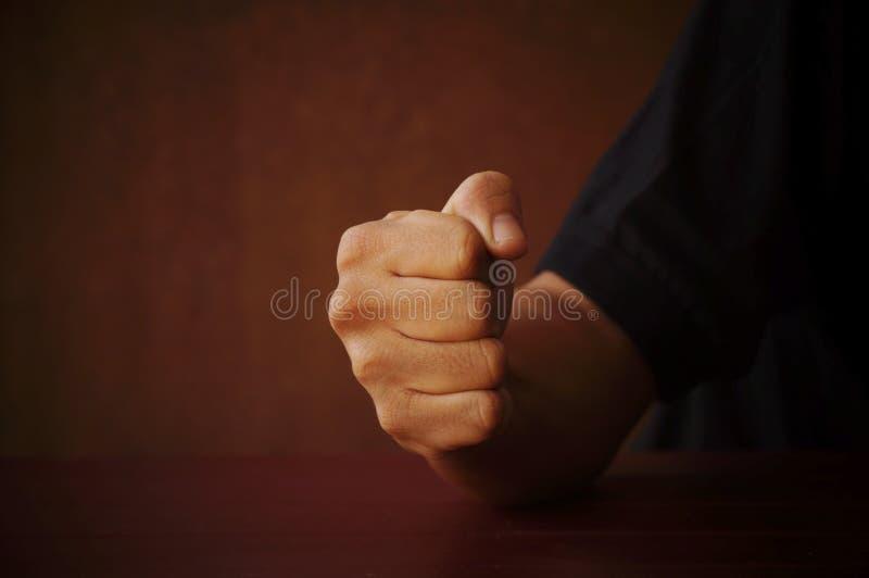 Faust des Mannes auf Tabelle, Konzept in der Energie des Kämpfers im dunklen Ton lizenzfreie stockfotografie