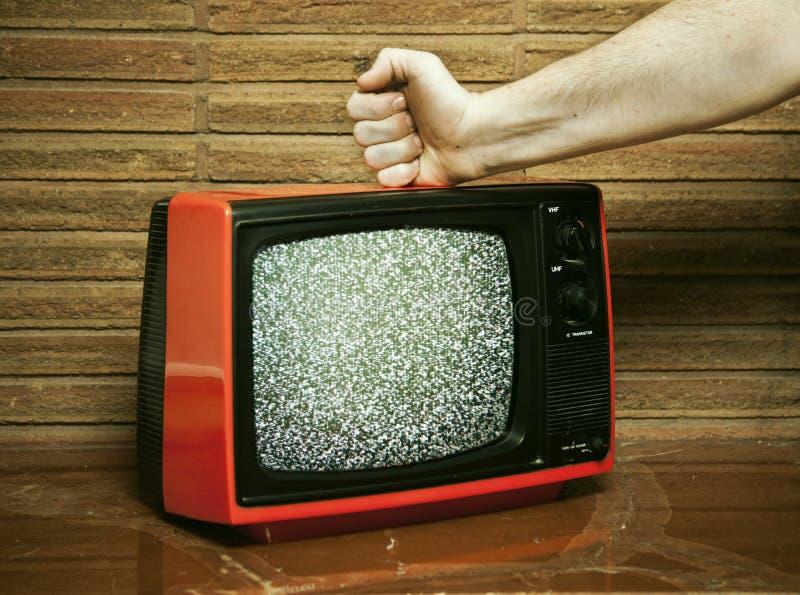 Faust, die einen Fernsehapparat zertrümmert stockbilder