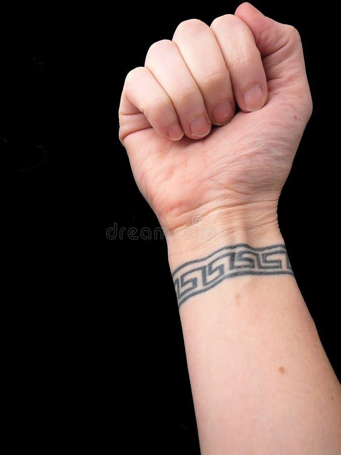 Faust mit Handgelenk-Tätowierung im griechischen Schlüsselmuster über schwarzem Hintergrund stockbild