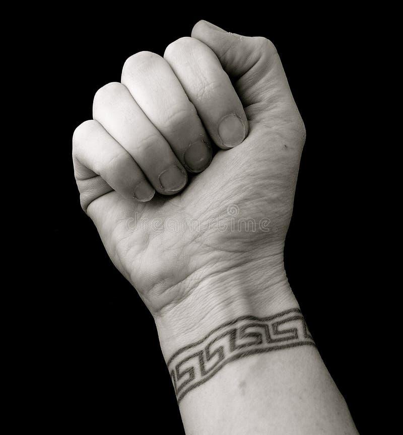 Faust mit Handgelenk-Tätowierung im griechischen Schlüsselmuster über schwarzem Hintergrund stockfotos