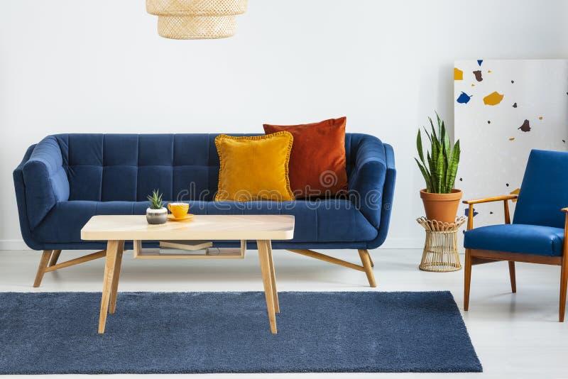 Fauteuil à côté de sofa bleu avec des coussins et de table en bois dans à plat intérieur avec l'usine Photo réelle photo libre de droits