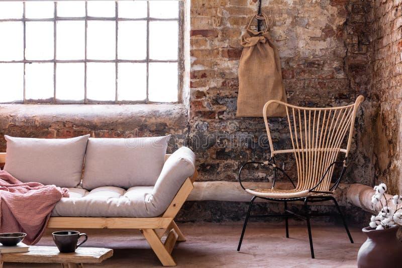 Fauteuil à côté de sofa gris avec des coussins dans l'intérieur industriel avec la fenêtre et le mur de briques rouge photo stock
