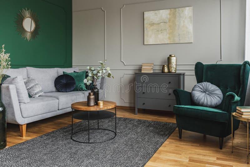 Fauteuil arrière d'aile vert émeraude avec oreiller dans le salon gris intérieur avec commode en bois photos libres de droits