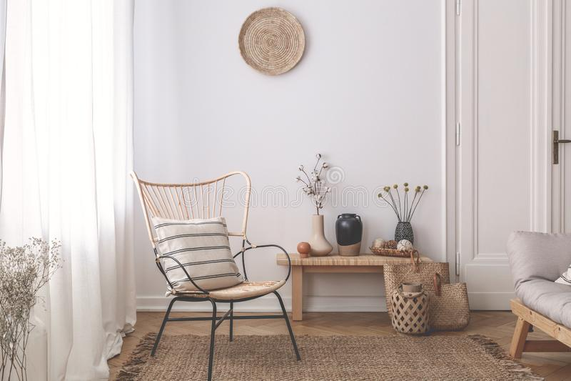 Fauteuil avec l'oreiller sur la couverture brune dans l'intérieur naturel blanc de salon avec des usines Photo réelle images stock