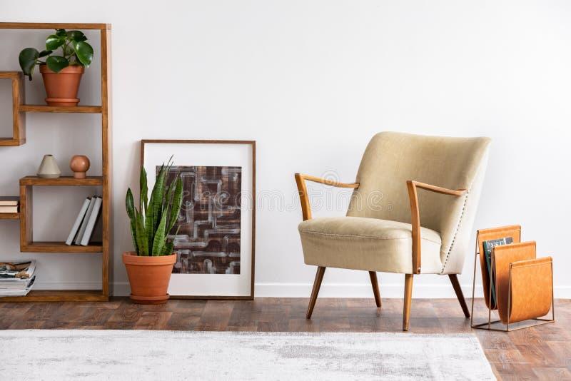 Fauteuil beige à côté d'affiche et d'usine en appartement blanc intérieur avec le tapis et les étagères Photo réelle photo stock