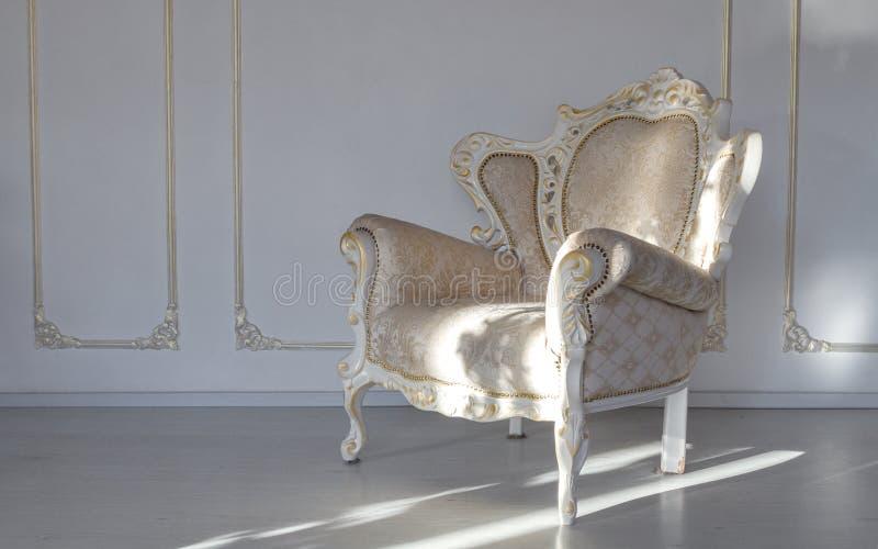Fauteuil blanc de tissu classique dans la chambre blanche images libres de droits