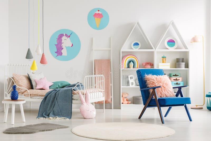 Fauteuil bleu à côté de lit avec la couverture dans le bedro coloré du ` s d'enfant photo stock