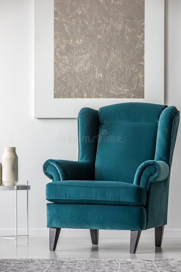 Fauteuil bleu de velours dans l'intérieur blanc élégant avec la peinture argentée abstraite sur le mur image libre de droits