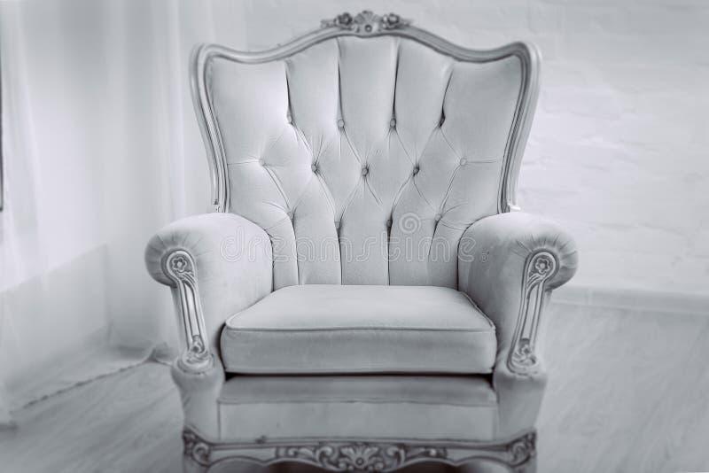Fauteuil en bois en cuir beige avec le décor d'or dans un salon blanc images libres de droits